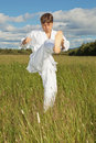 Young man in white kimono trains to beat foot Royalty Free Stock Photography