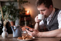A young man in a white shirt and waistcoat breakfasts Royalty Free Stock Photo