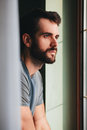 Young man by the window looking outside Royalty Free Stock Photo