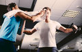 Young man wiping sweat off of friend s face in gym men Royalty Free Stock Photo
