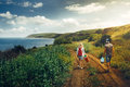 Young Man and Woman with Backpack, view from behind, Walking along the Road Towards the Sea Adventure Travel Relax Concept Royalty Free Stock Photo