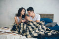 A young man and a woman are drinking coffee in the morning in bed. Romantic morning at home Royalty Free Stock Photo