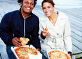 Young man and woman eating pizza outdoors Royalty Free Stock Image