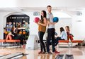 Young man and woman holding bowling balls in club portrait of men women with friends background at Royalty Free Stock Images