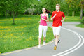 Young man and woman jogging outdoors Stock Photos