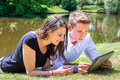 Young man and woman lying at water reading Ipad Royalty Free Stock Photo