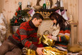 Young man and woman opening Christmas gifts Royalty Free Stock Photo