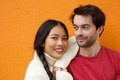 Young man and woman posing against orange background Royalty Free Stock Photo