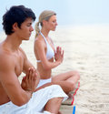 Young man and woman sitting at the beach Stock Photo