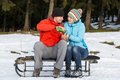 Young man and woman sitting on a sledge and sharing a cup of hot men women tea from thermos Royalty Free Stock Photos