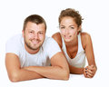 Young man and woman together over white background lovely couple lying on the floor isolated on Stock Image