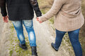 Young man and woman walking along countryside road holding hands Royalty Free Stock Photo