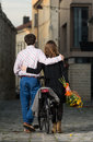 Young man and woman walking away together men women on a street in the city center they have a city bicycle she is holding a Royalty Free Stock Image