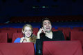 Young man and woman watch movie and laugh in movie theater happy men women Stock Images