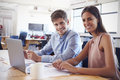 Young man and woman working in office smiling to camera Royalty Free Stock Photo