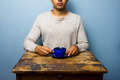 Young man at wooden table drinking from cup a Royalty Free Stock Image