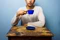 Young man at wooden table drinking from cup a Royalty Free Stock Photography