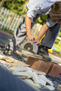 Young man working in his back yard using circular saw Royalty Free Stock Photo