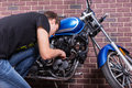 Young Man Working on his Blue Custom Motorcycle Royalty Free Stock Photo
