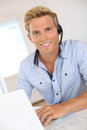 Young man working in office with headset smiling attractive customer service representative Stock Photography
