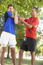 Young man working with personal trainer in park Royalty Free Stock Photography