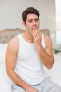 Young man yawning in bed at home sitting and Royalty Free Stock Image