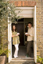 Young man and young pregnant woman standing in doorway with tea cups, smiling, portrait Royalty Free Stock Photo