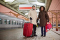 Young man and young woman stand with big red roll on bag men women railway platform holding hands Stock Photography