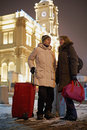 Young man and young woman stand with big red roll on bag men women railway platform in winter evening Royalty Free Stock Images