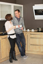 Young married couple enjoying a relaxing cup of coffee while standing chatting in their kitchen Stock Images