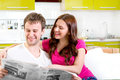 Young married couple in pajamas sitting in the sofa with newspap newspaper and coffee and having fun at home morning Stock Images