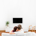 Young married couple sitting on the couch and watching tv at hom Royalty Free Stock Photo