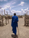 Young masai walking while showing his village in serengeti Royalty Free Stock Photo
