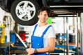 Young mechanic in blue overall working on car Royalty Free Stock Photo