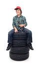 Young mechanic boy sitting on new car tires Royalty Free Stock Photo