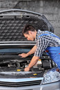 Young mechanic in overalls examining an automobile Stock Photo