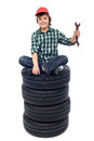 Young mechanic with tires and spanner car sitting isolated Royalty Free Stock Image