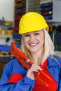 Young mechanic with yellow helmet and wrench in a workshop rare female occupations Stock Photo