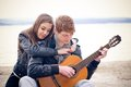 Young men acoustic guitar his girlfriend bach Royalty Free Stock Photo