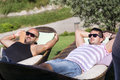 Young men enjoying the summer vacation laying on sunbed in a tropical garden friends relaxing Stock Photos