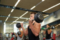 Young men flexing muscles with barbells in gym Royalty Free Stock Photo