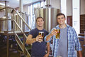 Young men holding a pint of beer smiling at camera Royalty Free Stock Photo