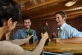 Young men laughing women drinking beer pub Stock Image
