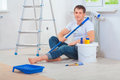 A young men painter sitting on floor holding paintroller and loo man looking at camera Stock Photos
