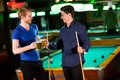 Young men playing pool and drinking beer Royalty Free Stock Photo