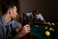 Young men playing snooker concentrating cue hand friend watching holding beer Royalty Free Stock Images