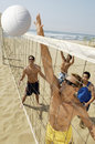 Young men playing volleyball on beach small group of Stock Images