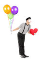 Young mime artist with balloons and red heart giving kisses full length portrait of a isolated on white background Royalty Free Stock Photos