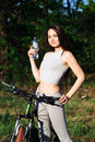 Young mixed race woman cyclist on mountain bike drinking water during cycling workout outdoor. Royalty Free Stock Photo