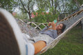 Young Mixed Race Woman Using Smartfone and Lying in Hammock in Park. Girl Chatting and Shopping Online, Using Digital Royalty Free Stock Photo